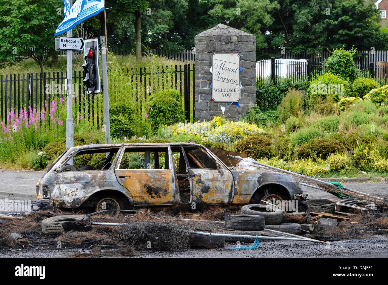 Belfast, Northern Ireland. 15th July 2013 - A burnt out car blocks the road at Mount Vernon following a night of - Stock Image