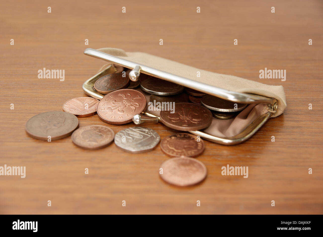 A purse filled with coins (British sterling money) spilling out onto a table Stock Photo