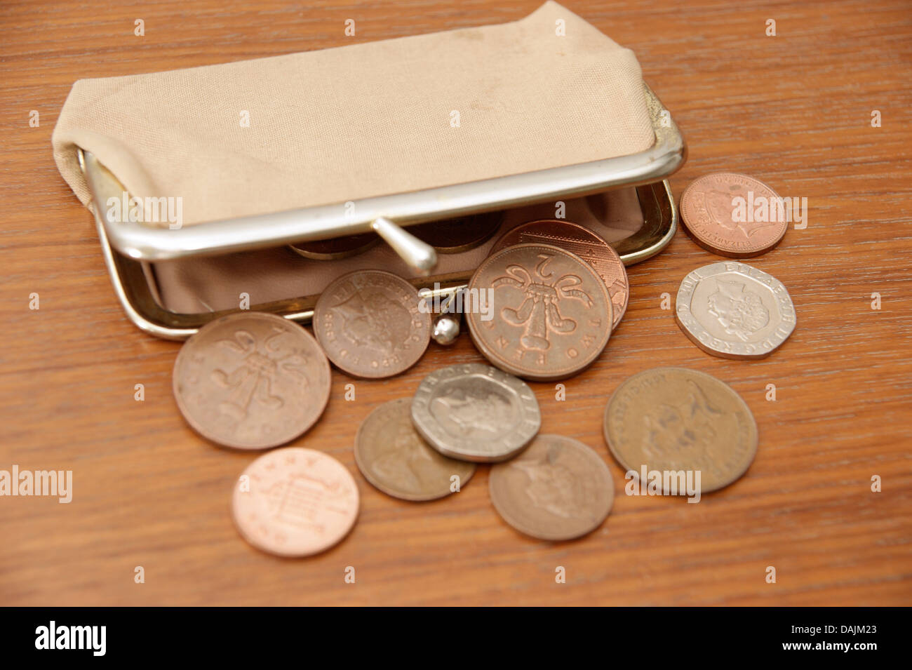 A purse filled with coins (British sterling money) spilling out onto a table - Stock Image