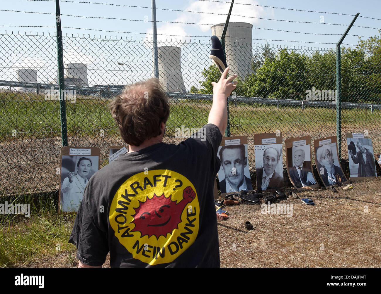 An anti-nuclear activist throws a shoe at a picture of French President Nicolas Sarkozy in Cattenom, France, 25 - Stock Image