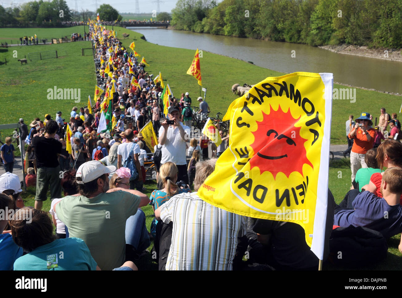 Anti-nuclear activists hold anti nuclear logo flags during a protest at the nuclear power plant Unterweser nearby - Stock Image