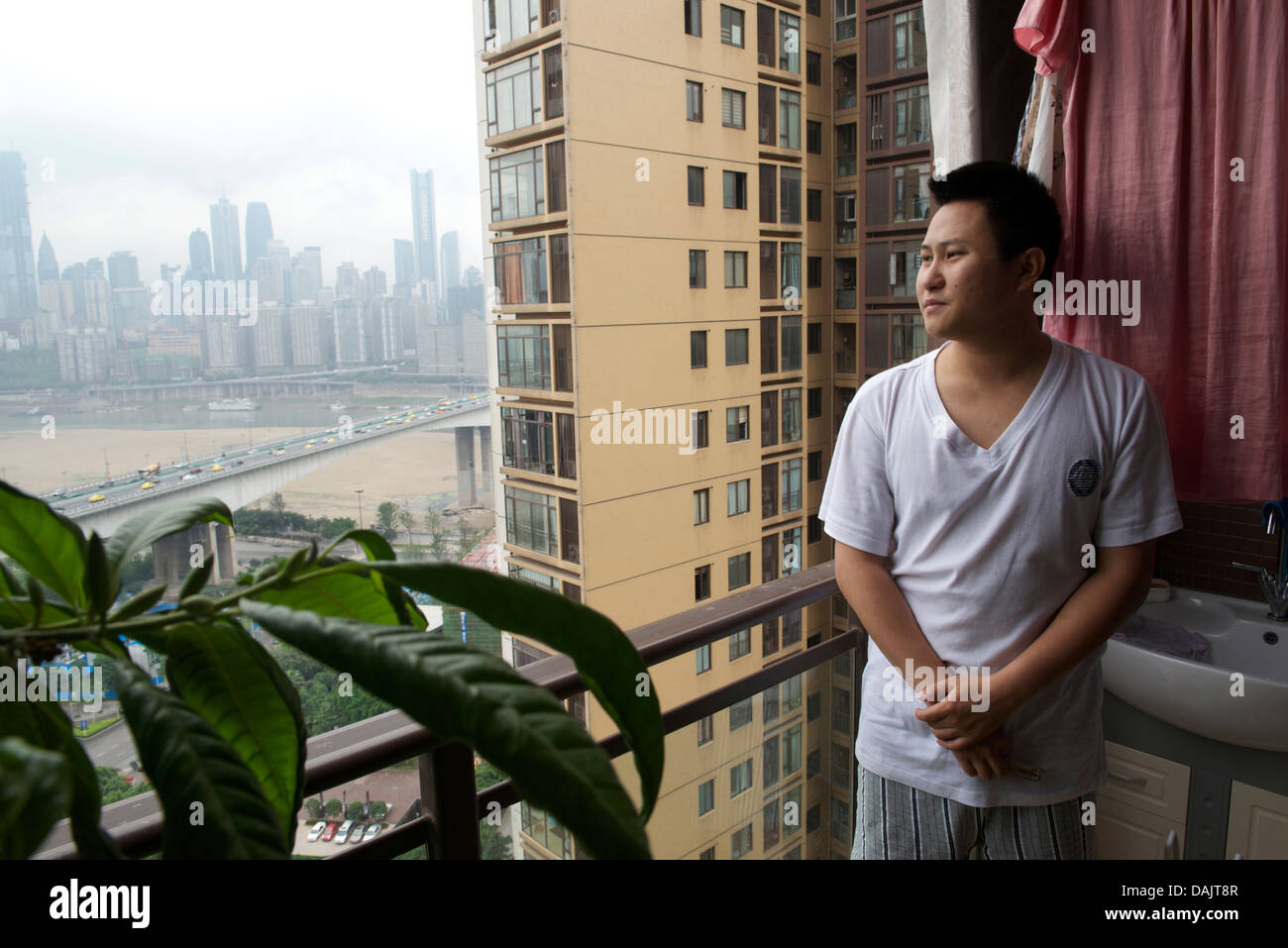 Chen Chao, 26 year old, overlooks Chongqing from the balcony of his new apartment in Chongqing, China. 09-May-2013 - Stock Image