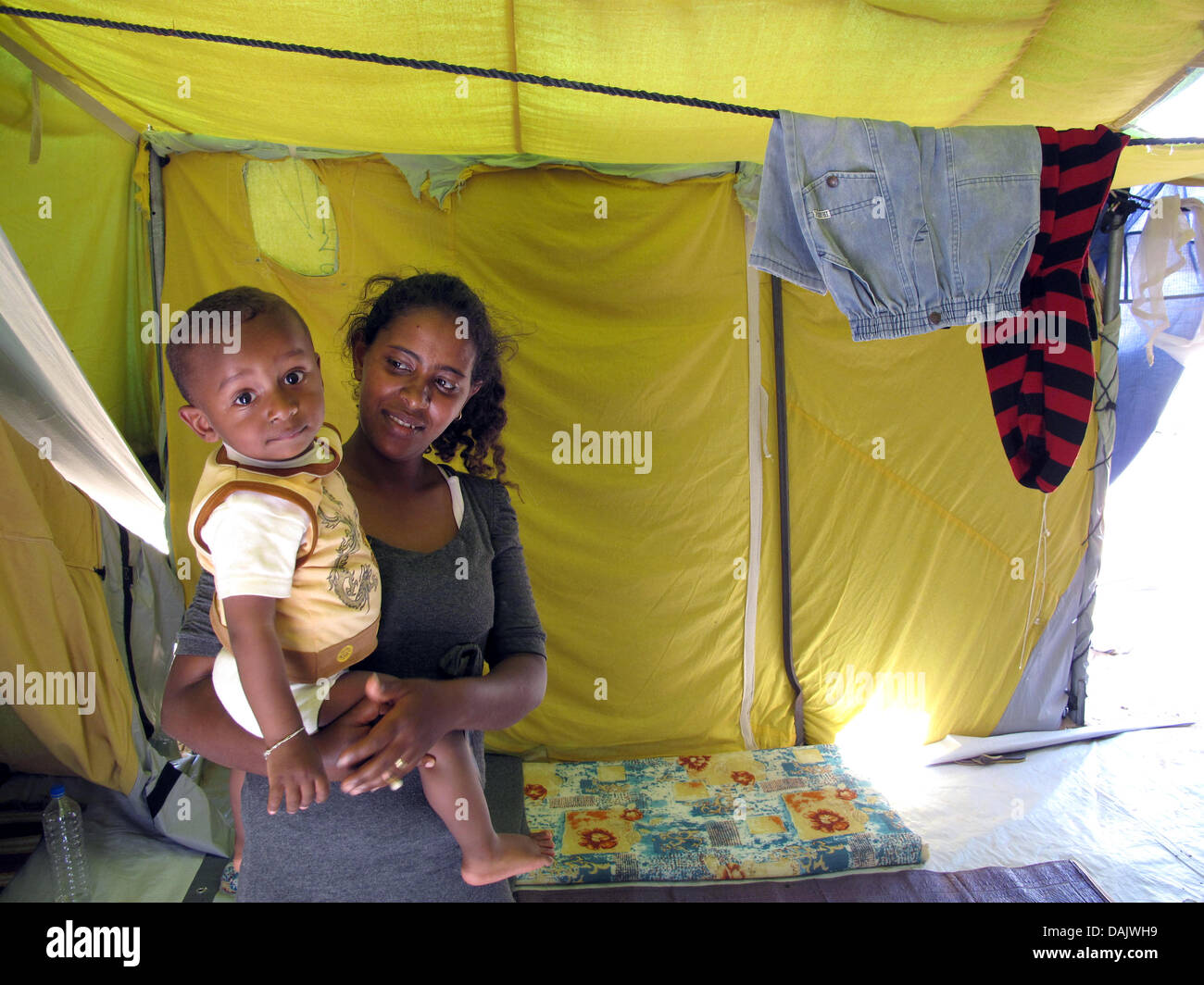 Besa (25) and her son Didia (1) from Ethyopia sit in their tent in the Shousha refugee camp on the border of Tunisia Stock Photo