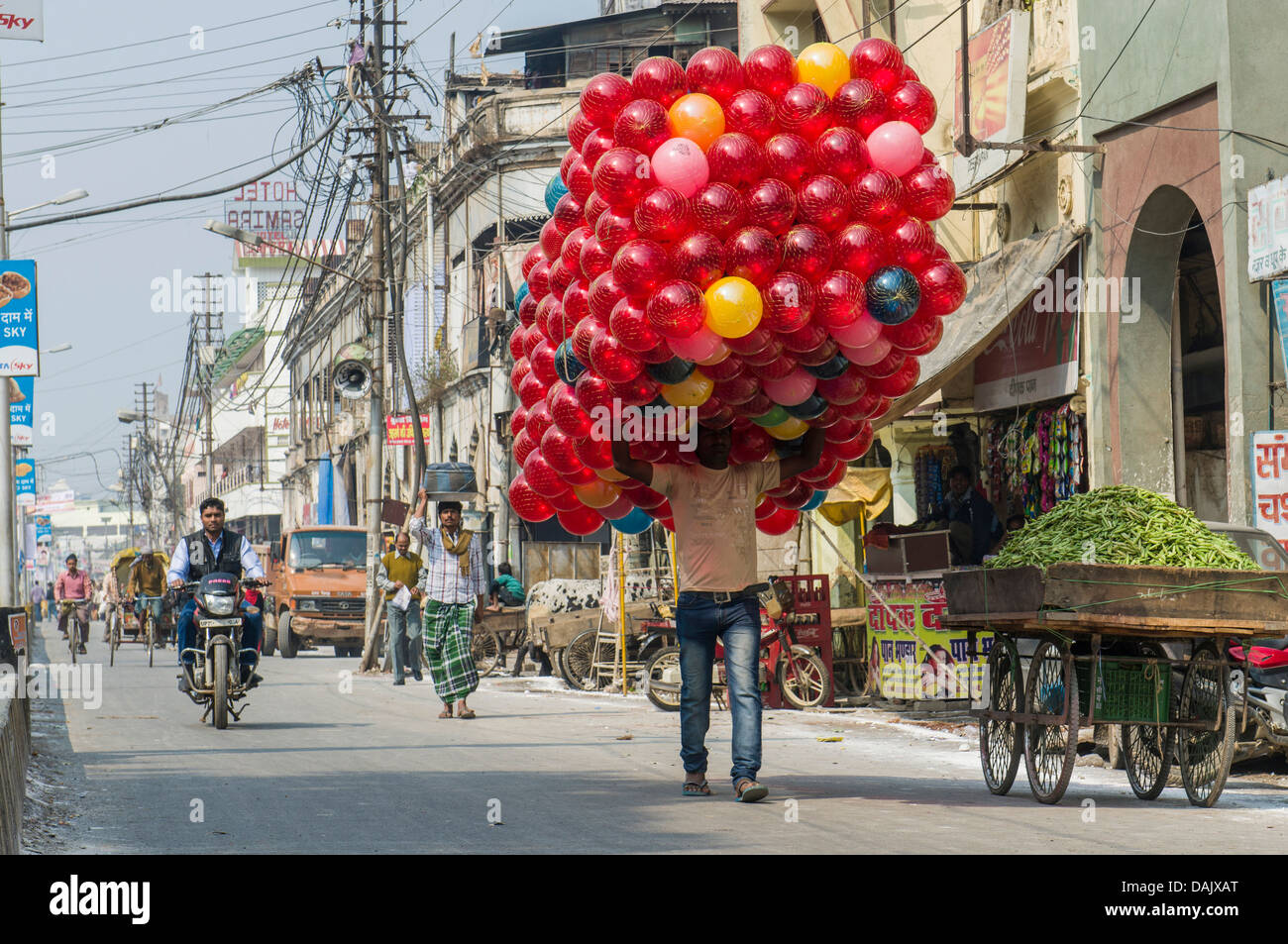 Man carrying a huge pack of red toy balls along a street Stock Photo