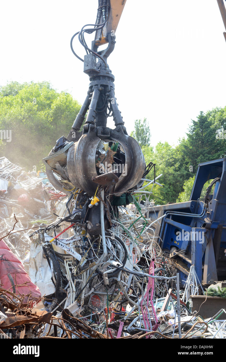 rubbish being processed by crane at scrapyard united kingdom - Stock Image