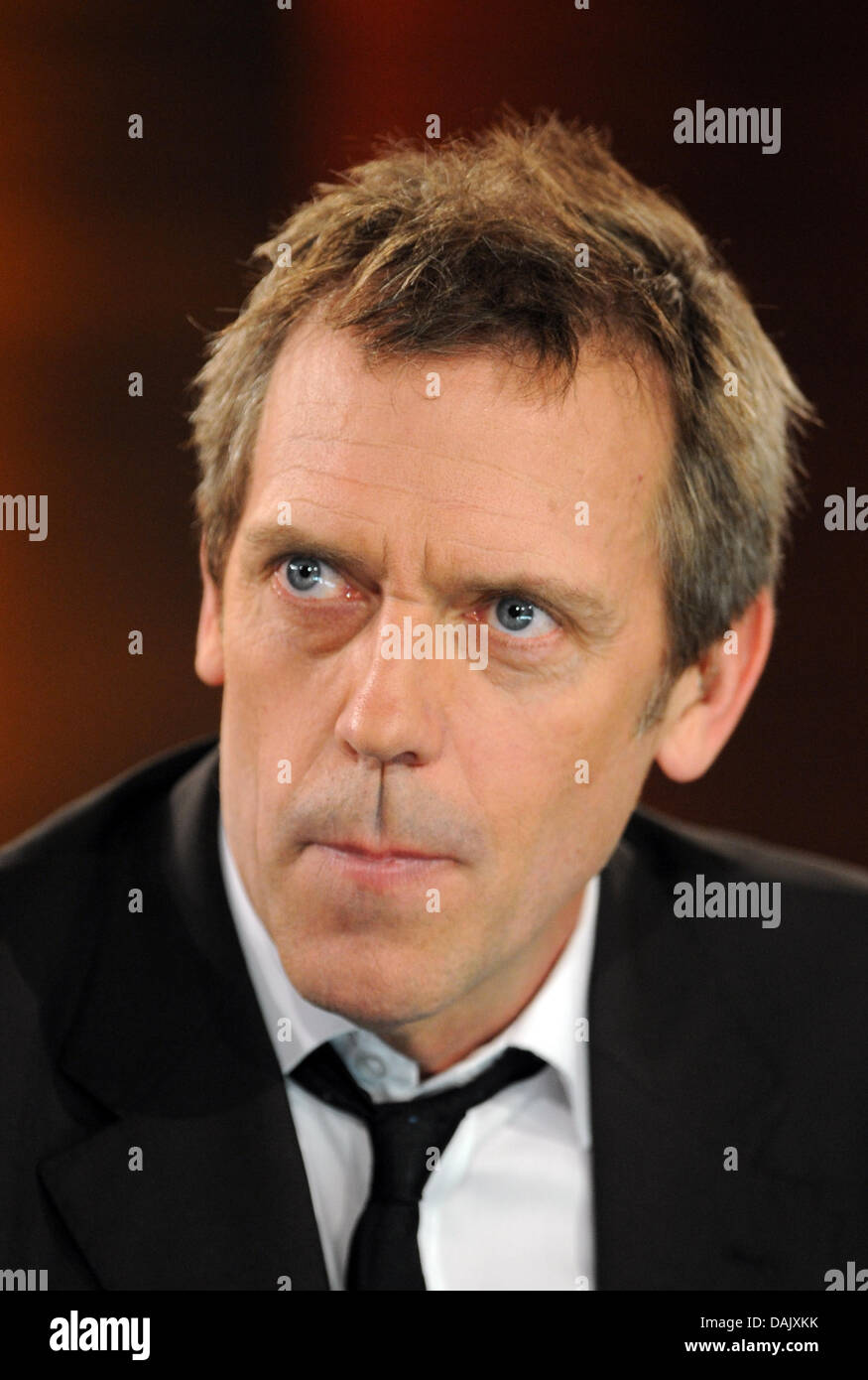 British actor and musician Hugh Laurie sits on the sofa during the ZDF German television show 'Wetten, dass...?' - Stock Image
