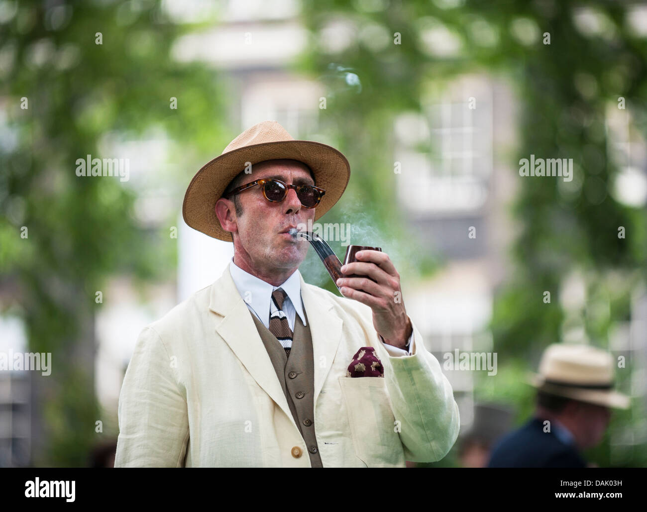 Gustav Temple, editor of the Chap magazine smoking the official pipe at the Chap Olympiad in Bedford Square Gardens. - Stock Image