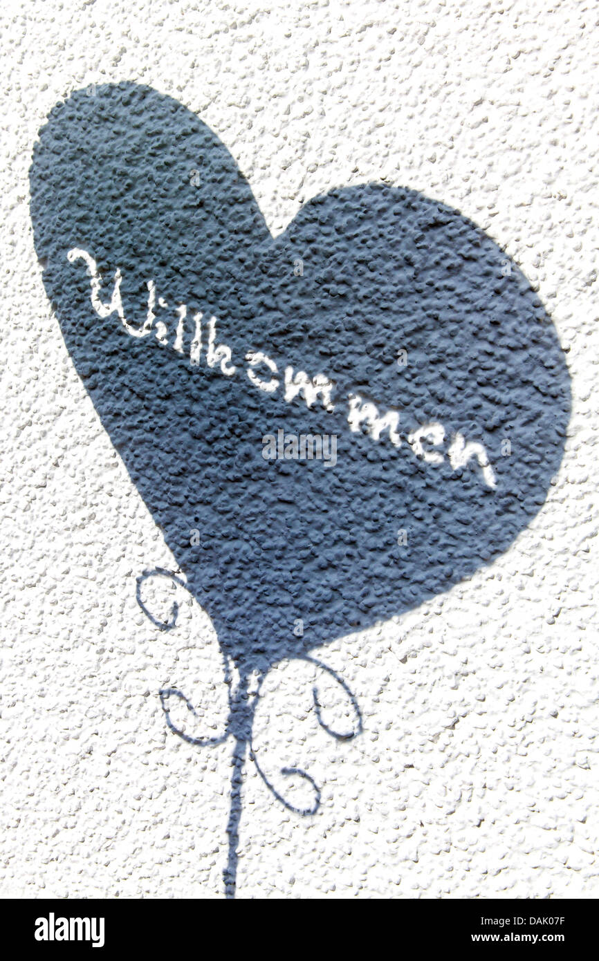 Heart with the word 'Willkommen', German for 'welcome', on a wall - Stock Image