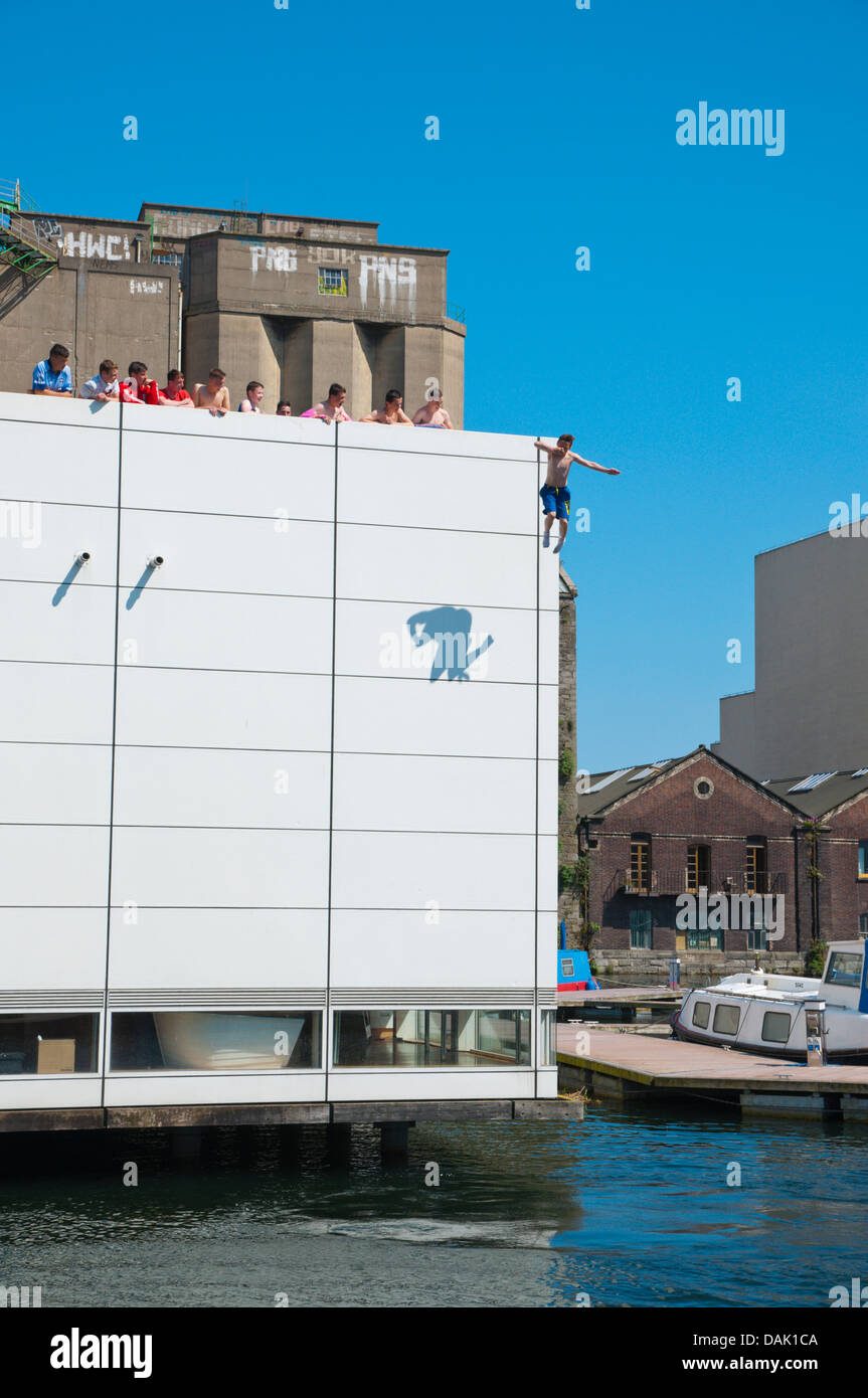 Local teenager jumping off Waterways visitor centre building Grand Canal Docks Docklands area central Dublin Ireland - Stock Image