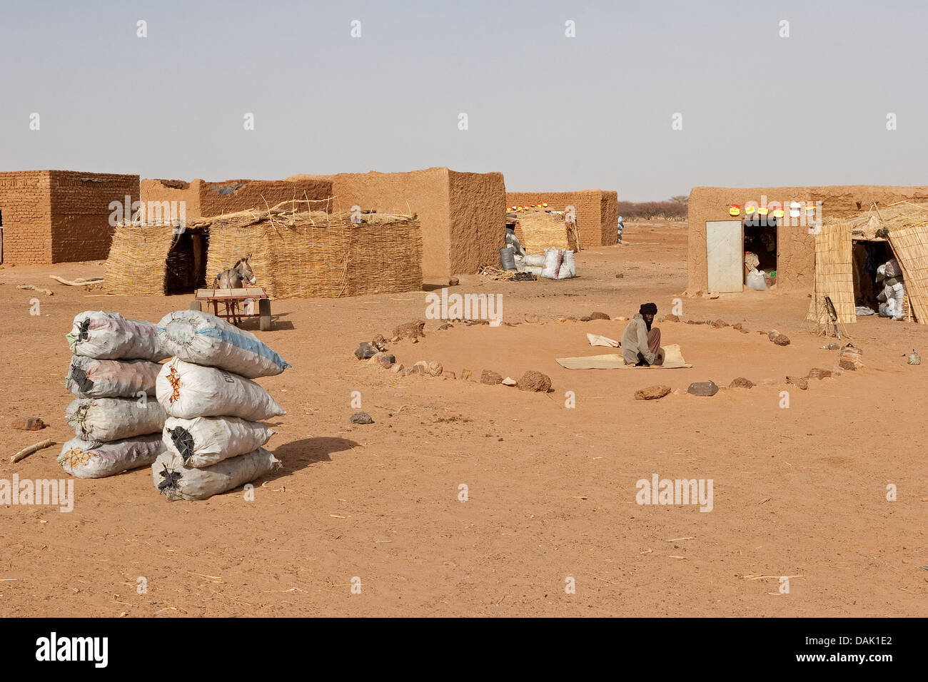 Malian village settlement on road to Gao with charcoal for sale and circle of stones as Mosque prayer area, Mali, - Stock Image