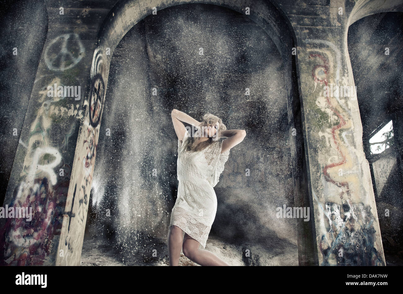 Woman in arch way with dust falling - Stock Image
