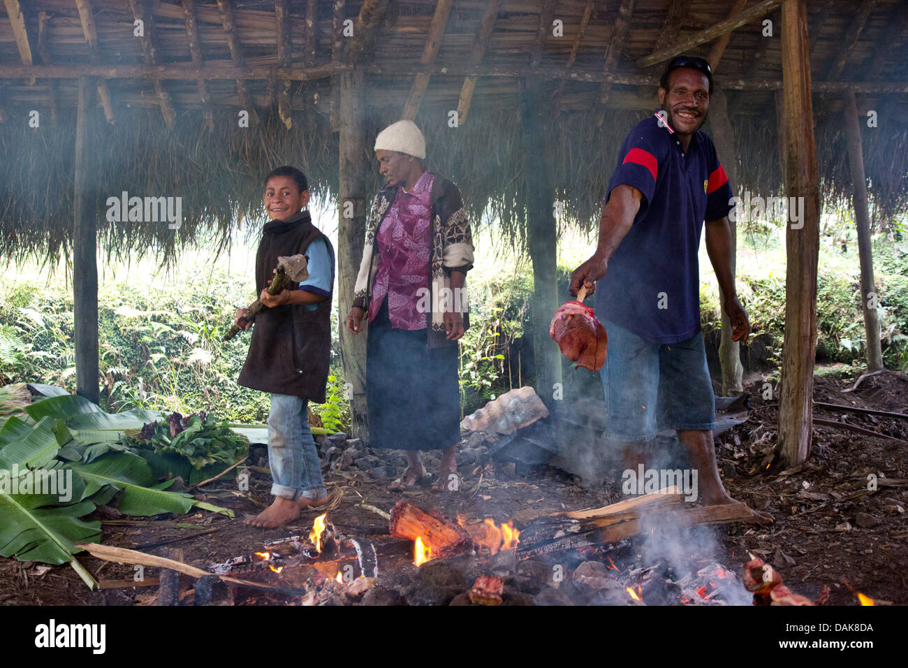 Men Cooking Using A Traditional Papua New Guinea Earth Oven Or Stock