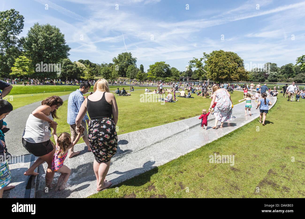 People enjoying summer  at Princess Diana Memorial Fountain, Hyde Park, London, England, UK - Stock Image