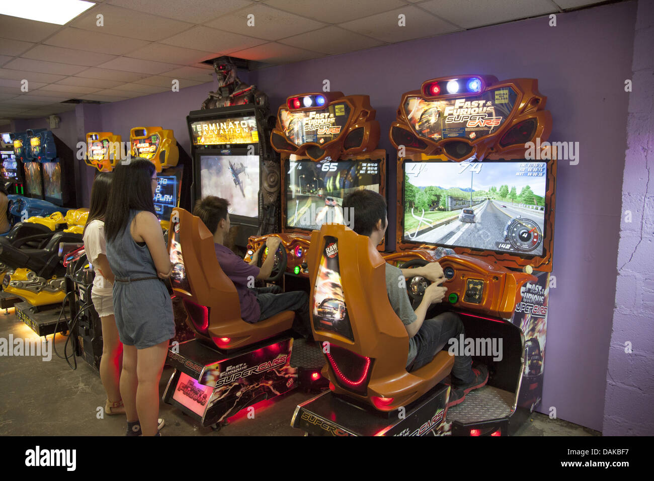 Teens get an adrenaline rush at the video arcade driving race cars at high speeds at Coney Island, - Stock Image