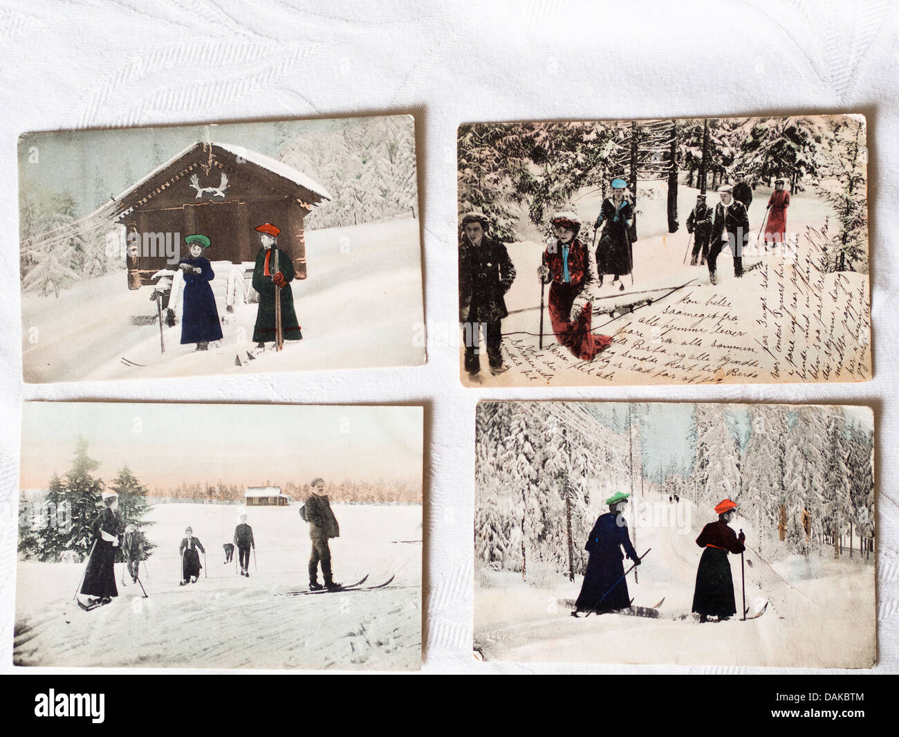 vintage postcards with Norwegian winter scene, men and women skiing in the woods, writing on front - Stock Image