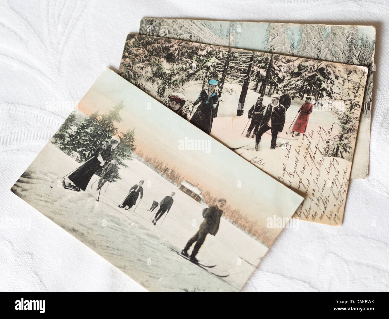 vintage postcards with winter scene, men and women skiing in the woods, writing on front - Stock Image