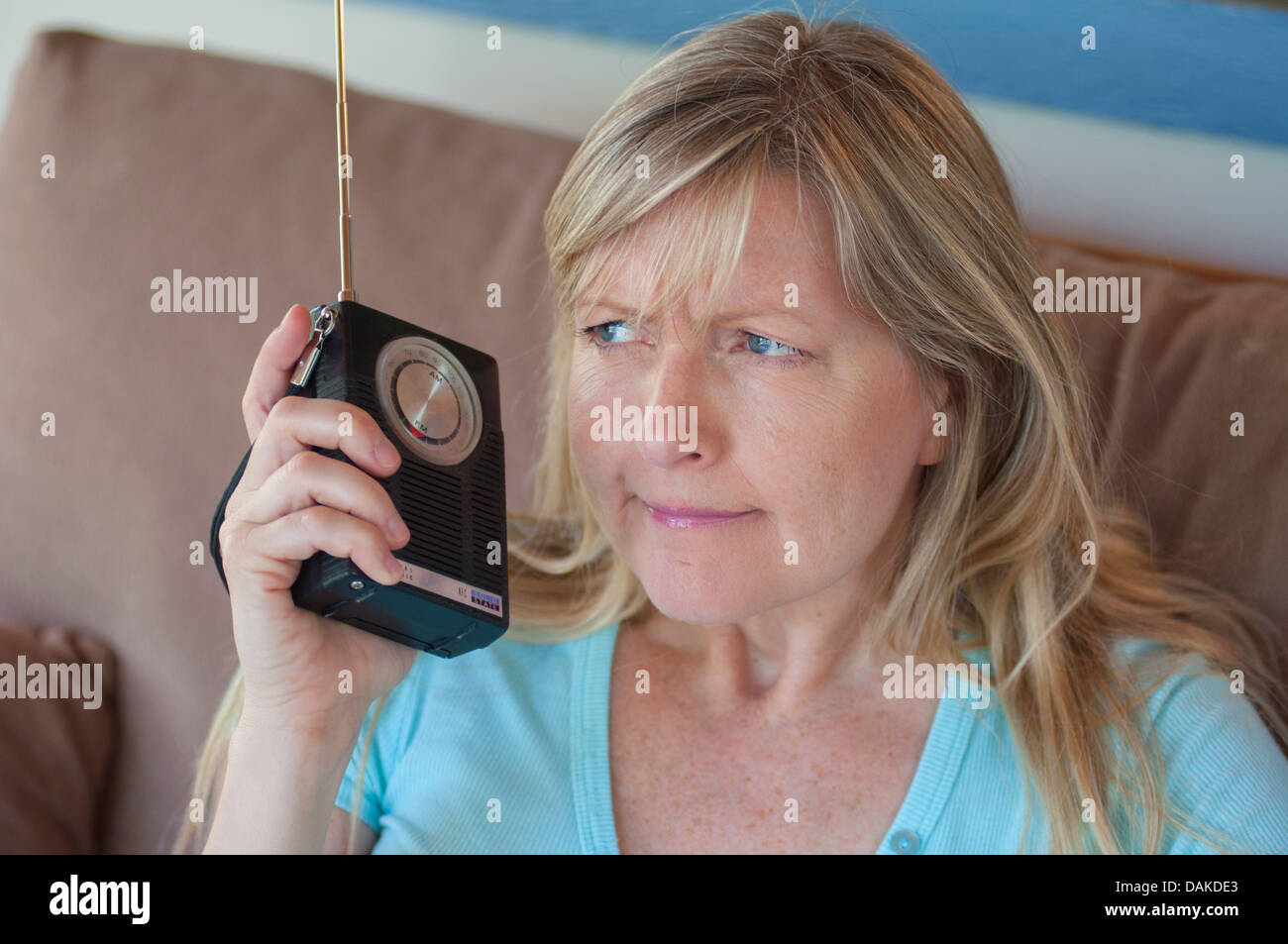 Woman with unsure expression listening to radio. - Stock Image
