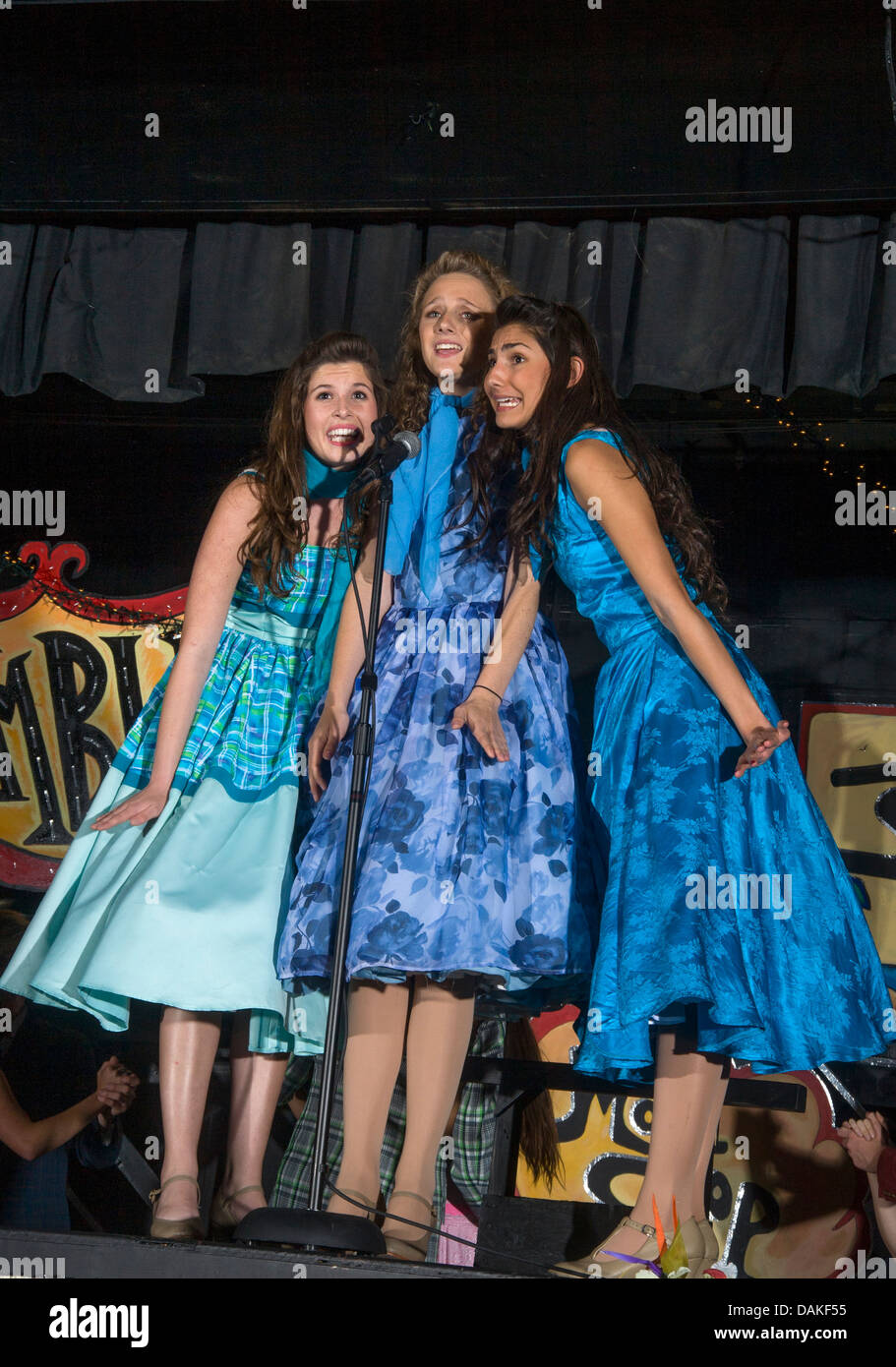 In 1950\'s dresses, a girls\' trio sings at the Rydell High School ...