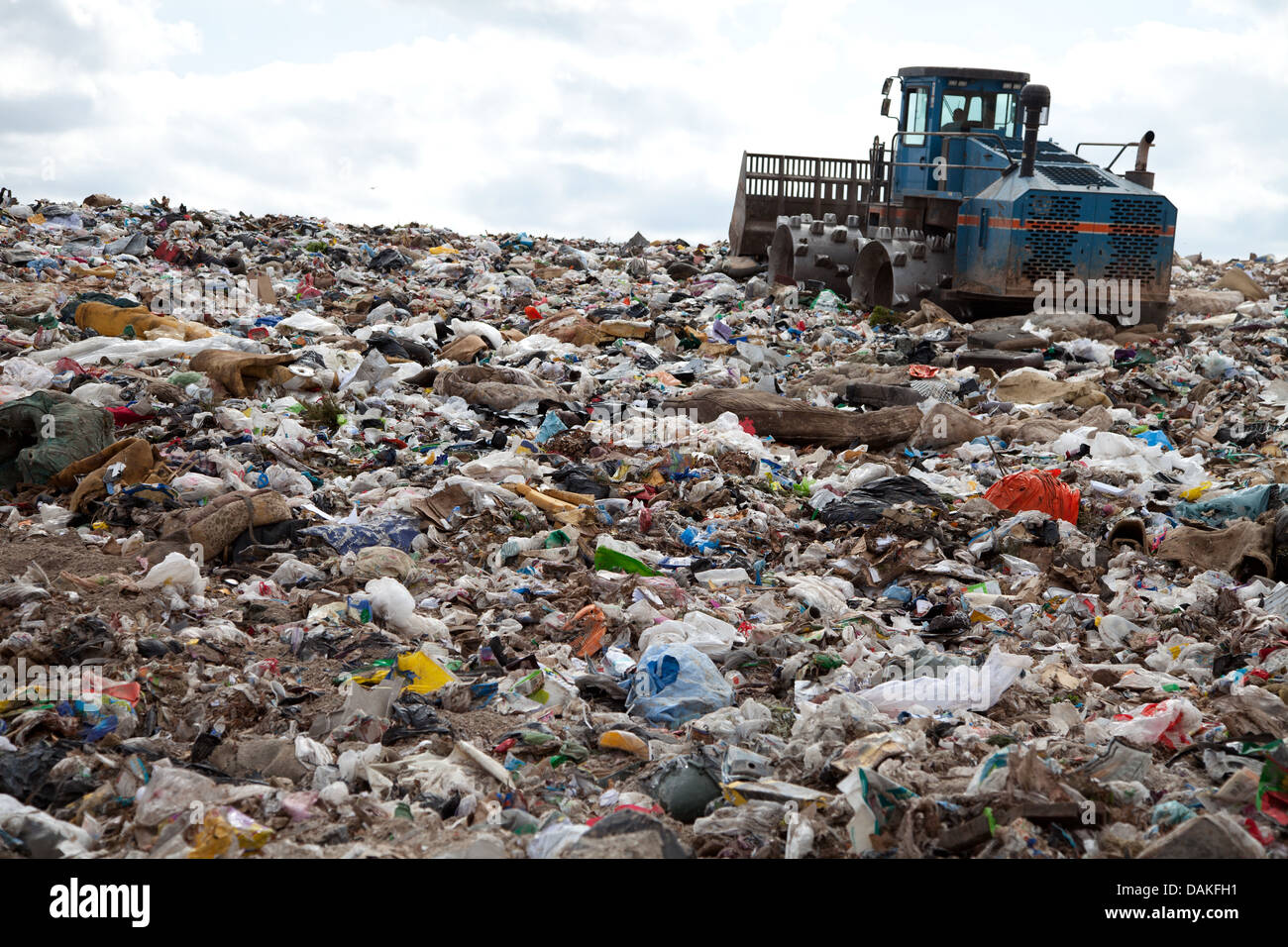 Garbage piles up in landfill site each day while truck covers it with sand for sanitary purpose - Stock Image