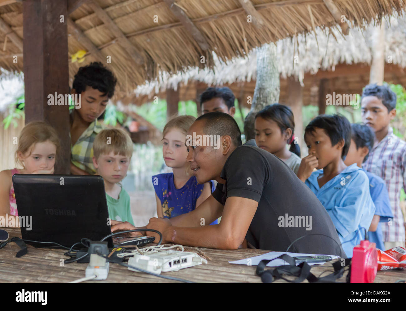 Local children and tourists gather round a laptop at Chambok Ecotourism Park, Cambodia, South East Asia - Stock Image