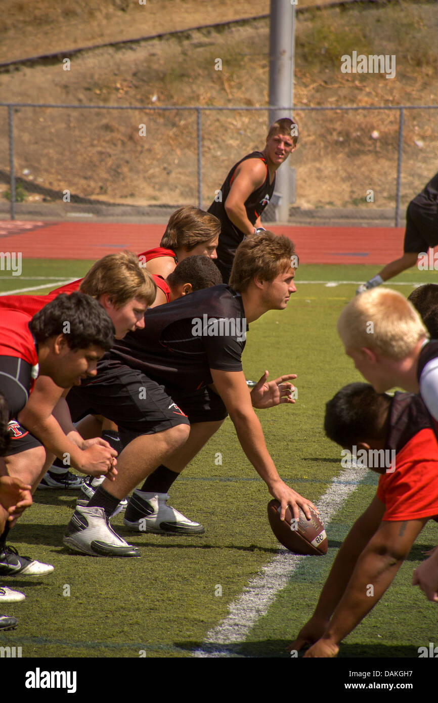 High school athletes at line of scrimmage during spring football practice in San Clemente, CA. - Stock Image