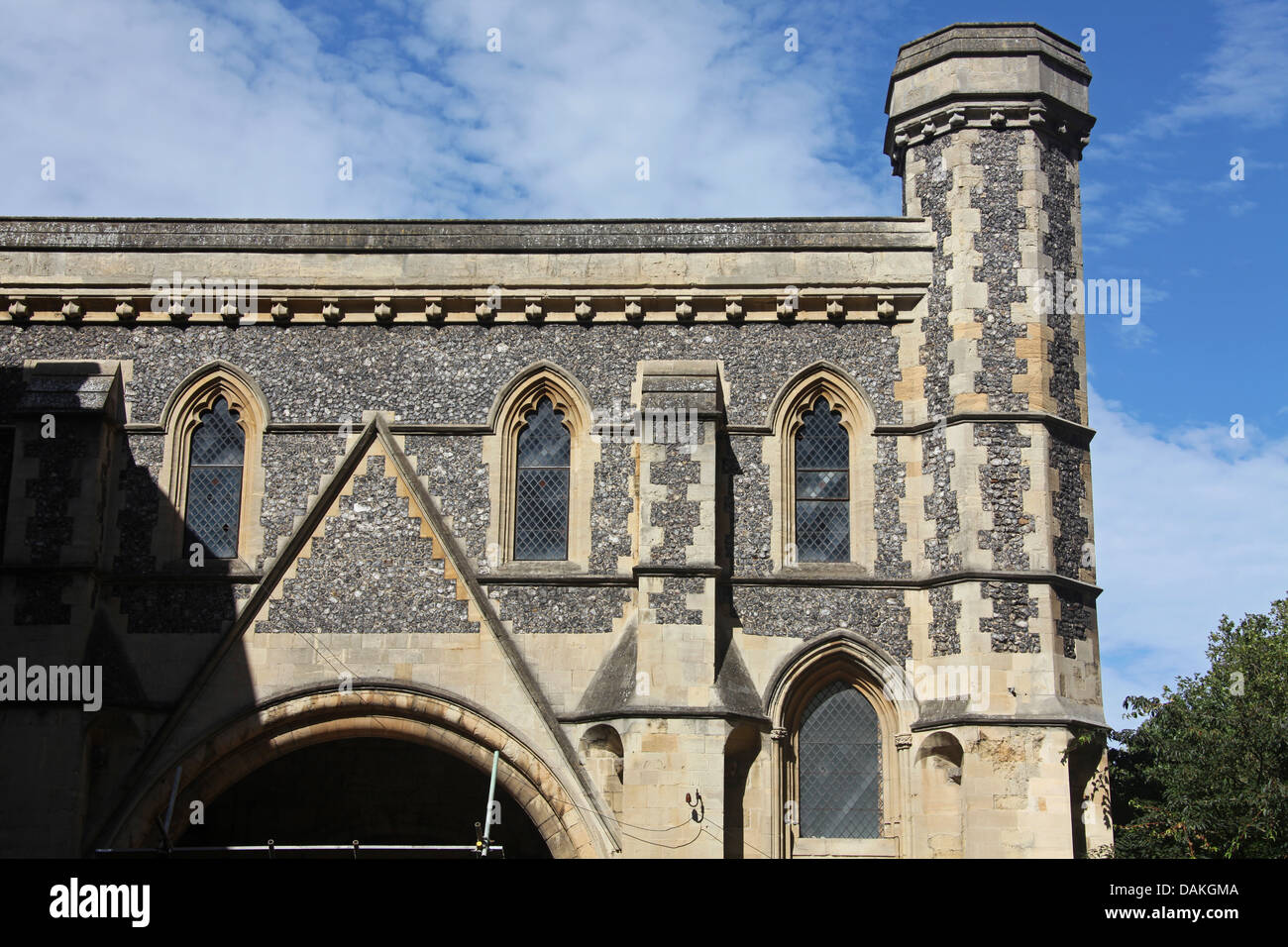 An old Gatehouse building constructed of Flint and cement complete with leaded glass windows, Gargoyles and a Tower. - Stock Image
