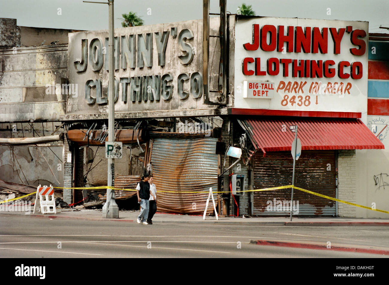 Hispanic youths pass fire damaged shops in South Central Los Angeles after the 1992 Rodney King race riot in Los - Stock Image