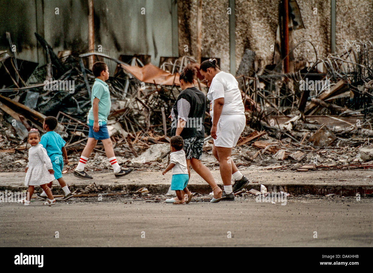 Hispanic locals walk past the ruins of a fire damaged shop in South Central Los Angeles after the 1992 Rodney King - Stock Image