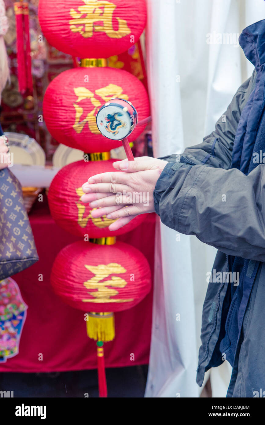 A Chinese man twirling a musical instrument during the London Chinese New Year 2013 - Stock Image