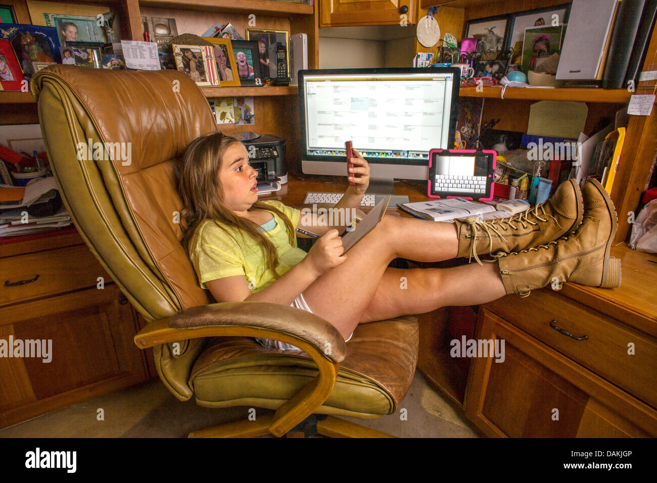 An eight-year-old girl multitasks with a computer, a tablet, a cell phone, and a writing pad at home in Laguna Beach, - Stock Image
