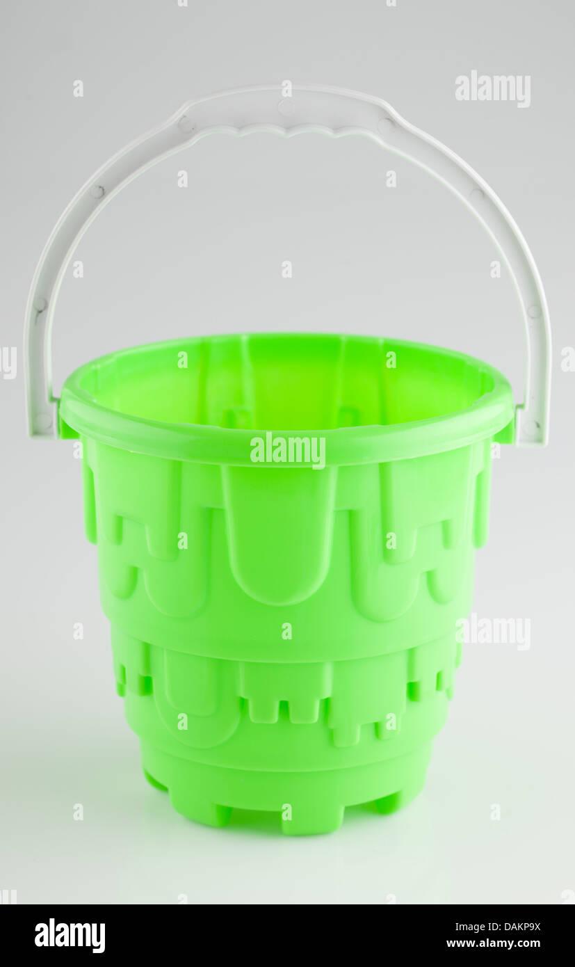 Green plastic sandcastle bucket - Stock Image