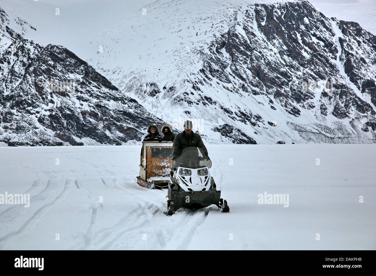 three persons with sleds in arctic landscape, Canada, Nunavut - Stock Image
