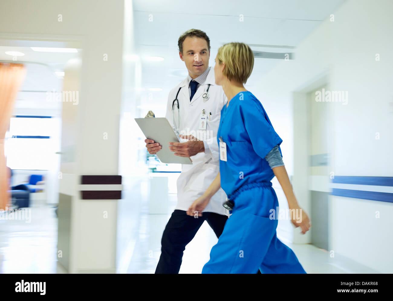 Doctor and nurse walking in hospital hallway - Stock Image