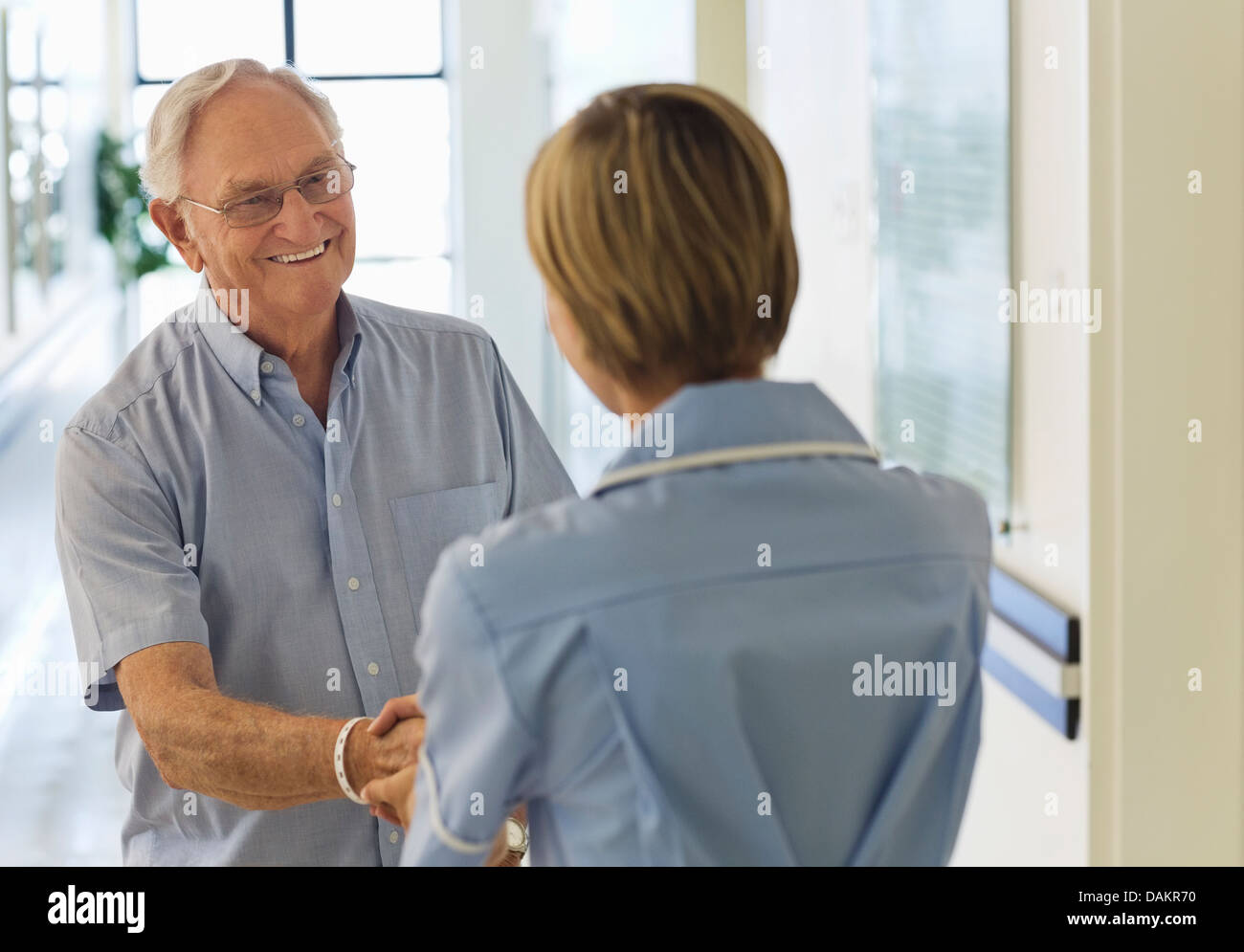Older patient and nurse shaking hands in hospital - Stock Image