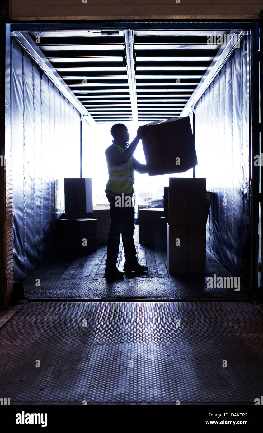 Worker stacking boxes in van Stock Photo