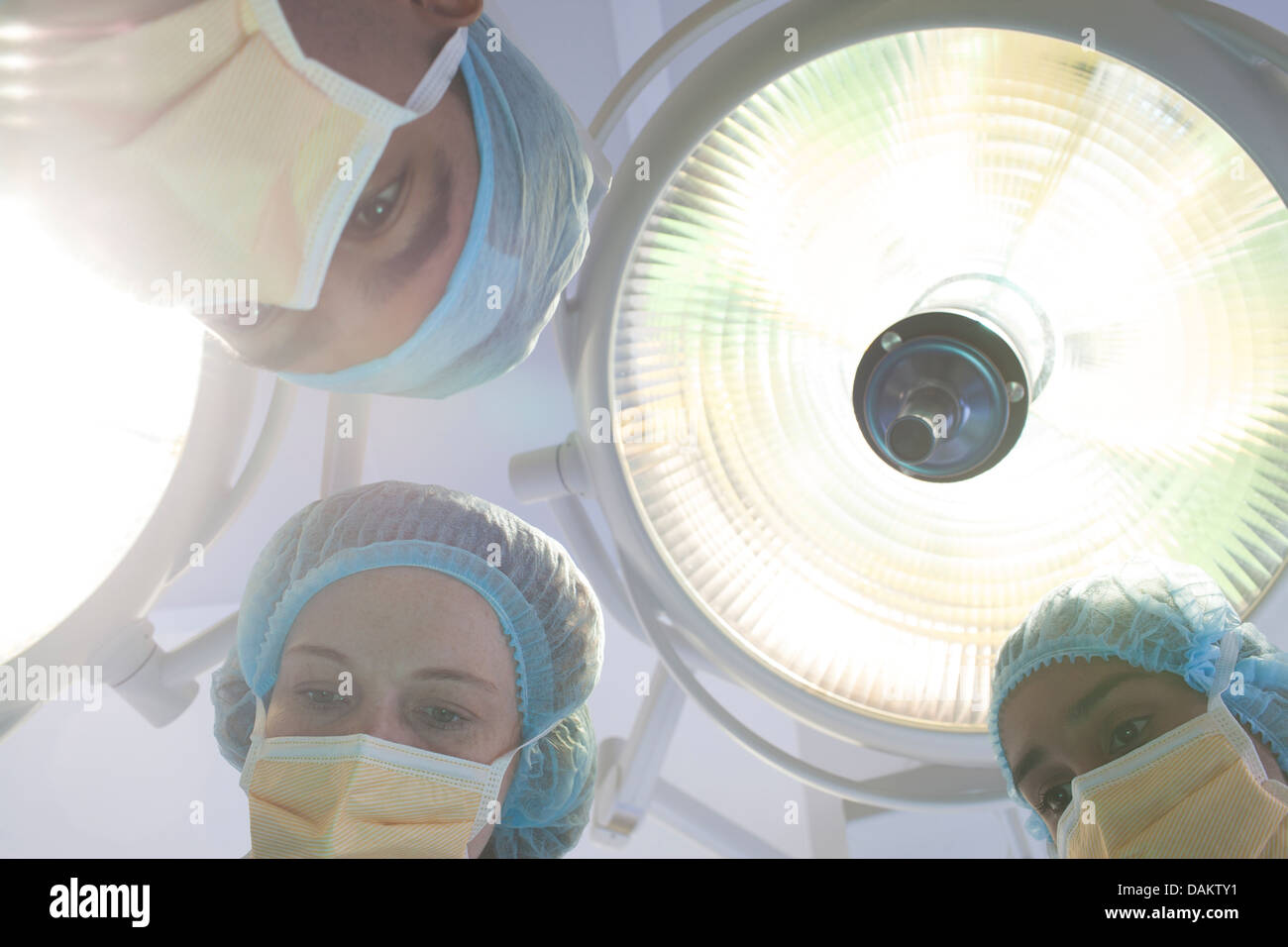 Surgeons bent over patient on operating table - Stock Image