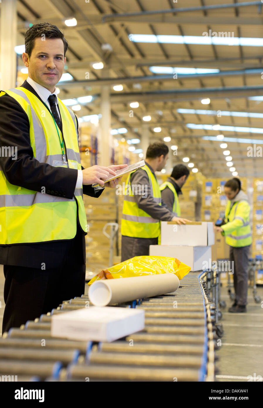 Workers checking packages on conveyor belt in warehouse - Stock Image