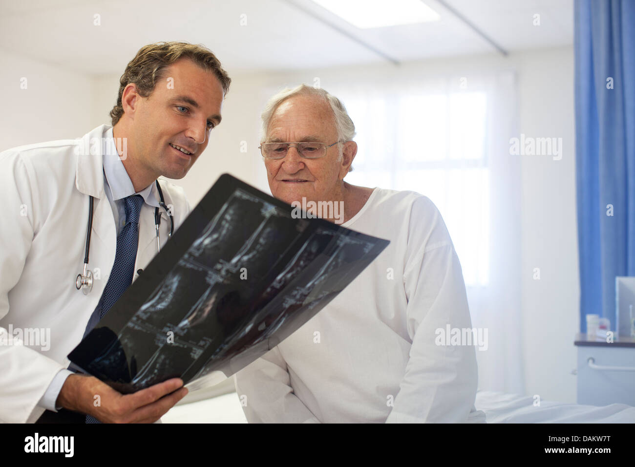 Doctor and patient examining x-rays in hospital room - Stock Image