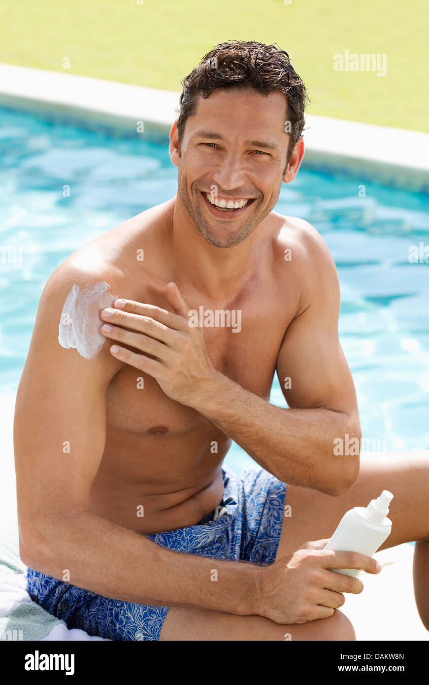 Man applying sunscreen by swimming pool - Stock Image