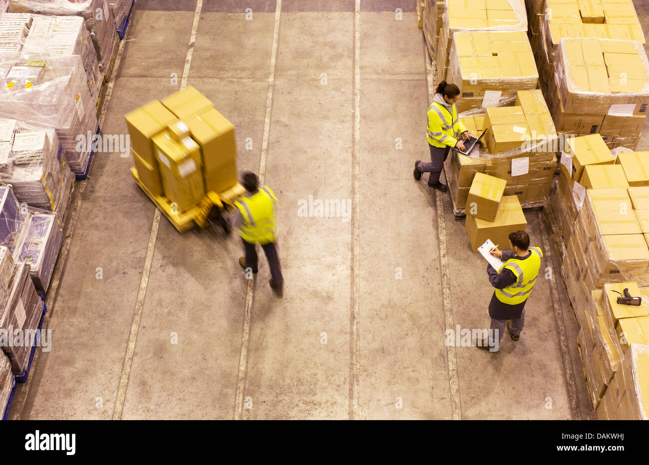 Workers carting boxes in warehouse - Stock Image