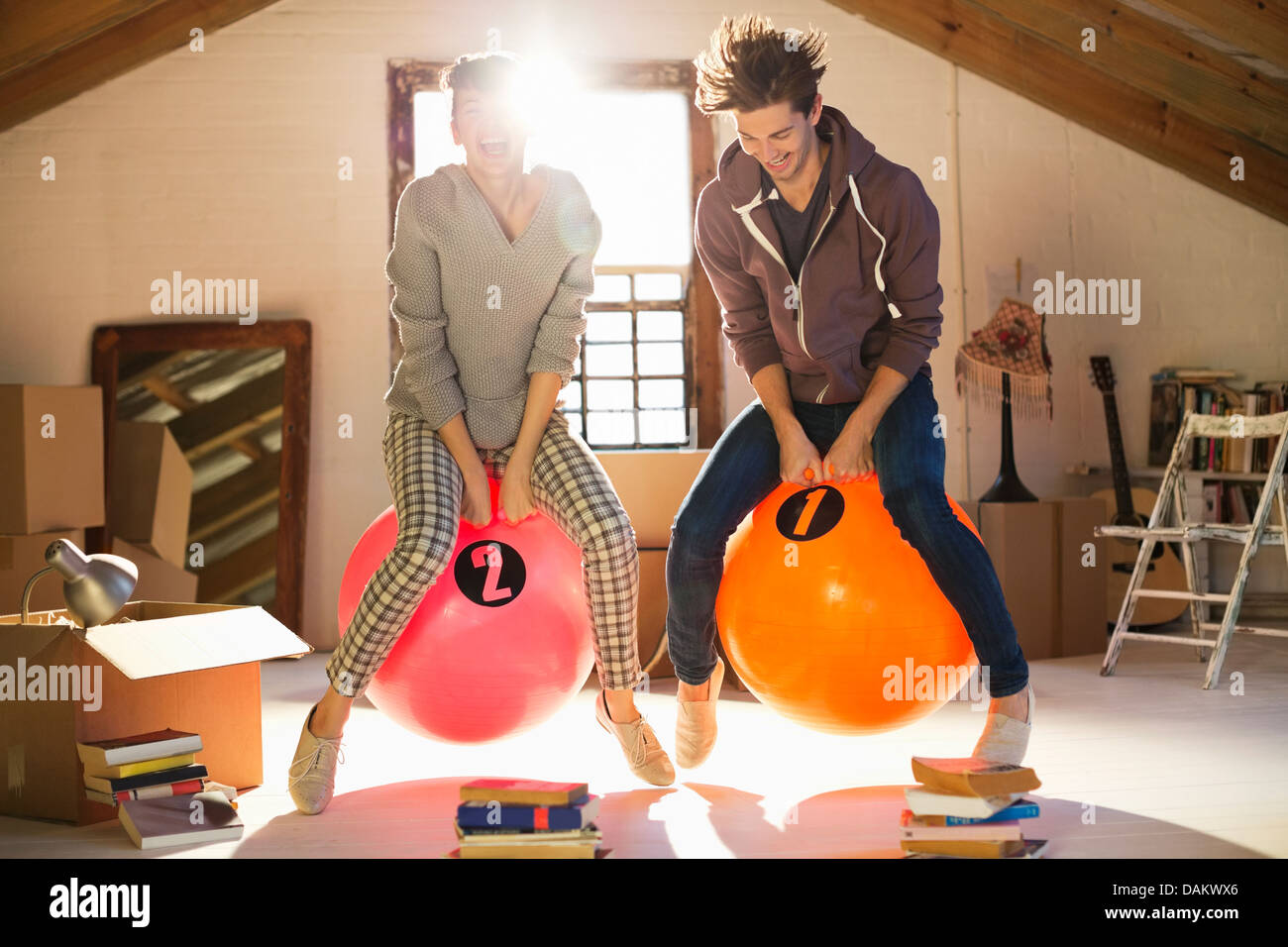 Couple jumping on exercise balls together Stock Photo