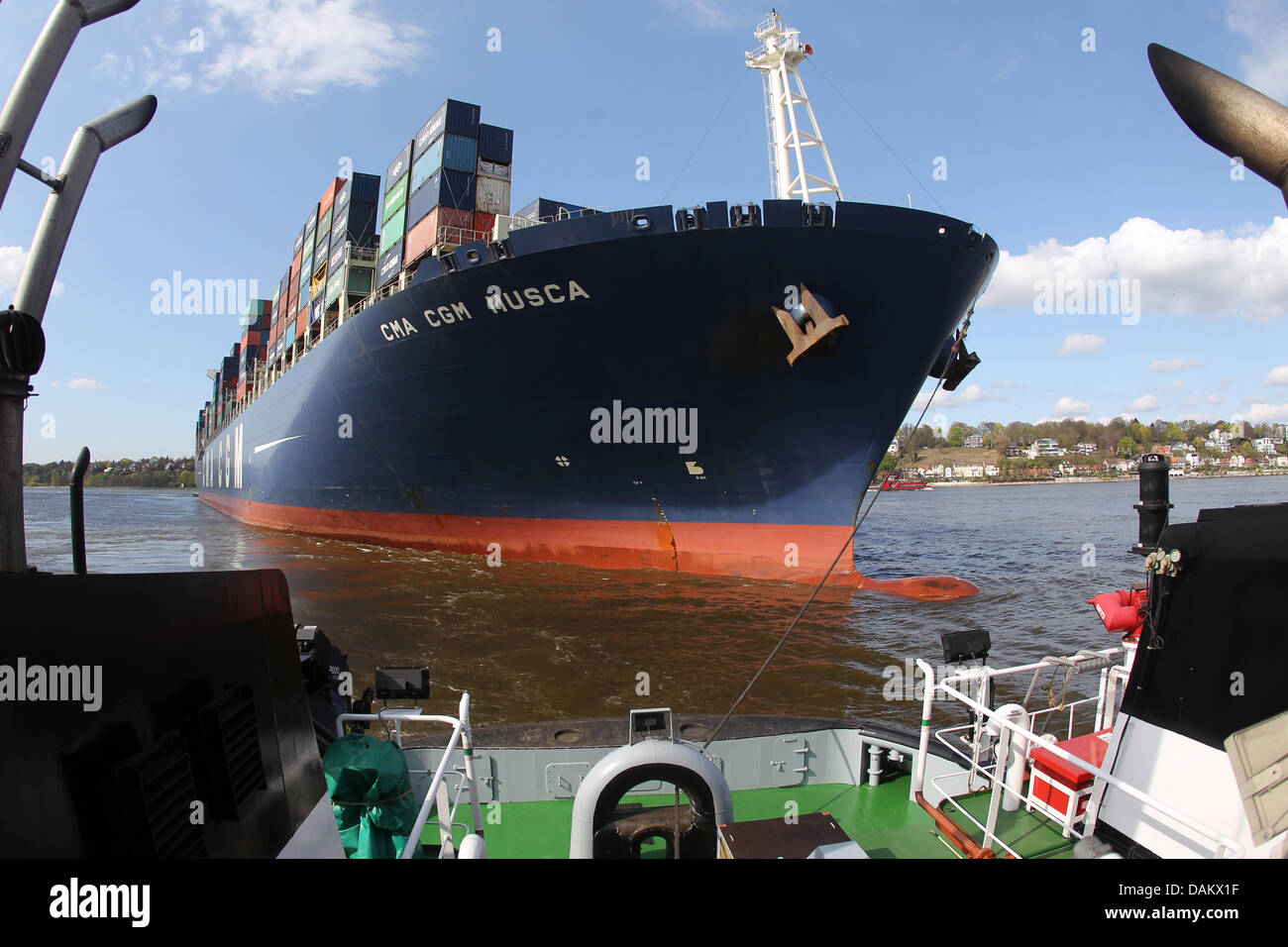 The tug boat Bugsier 5 takes the container ship CMA CGM Musca to it's anchor place at the harbour in Hamburg, - Stock Image