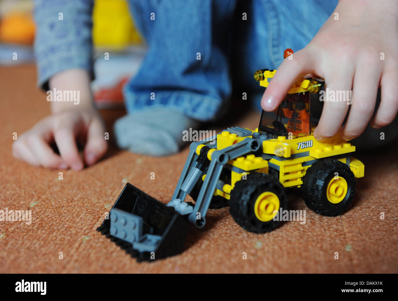 A little boy plays with a selfbuilt toy excavator from Lego in Berlin, Germany, 26 April 2011. Photo: Jens Kalaene - Stock Image