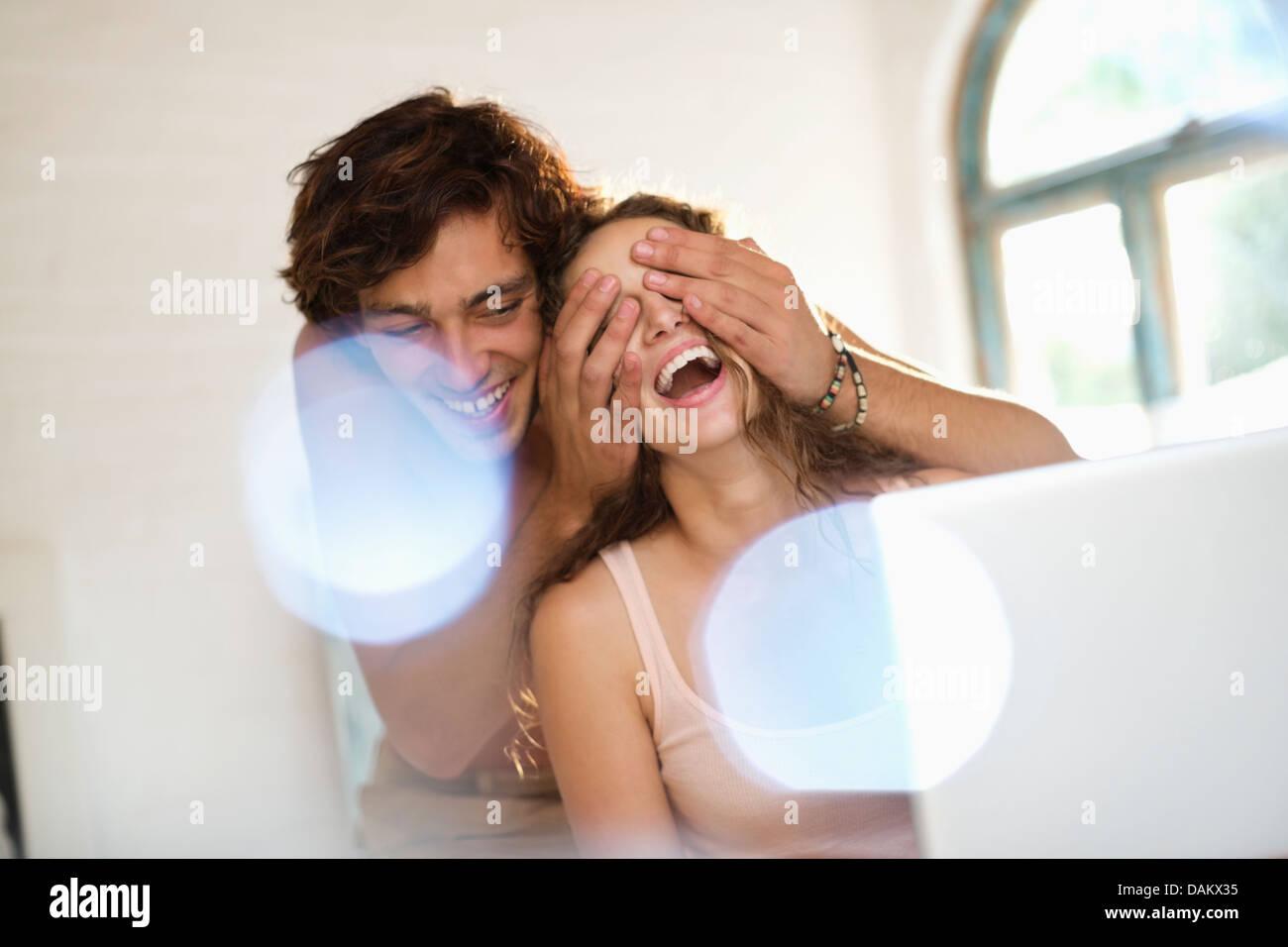Man covering girlfriend's eyes indoors - Stock Image