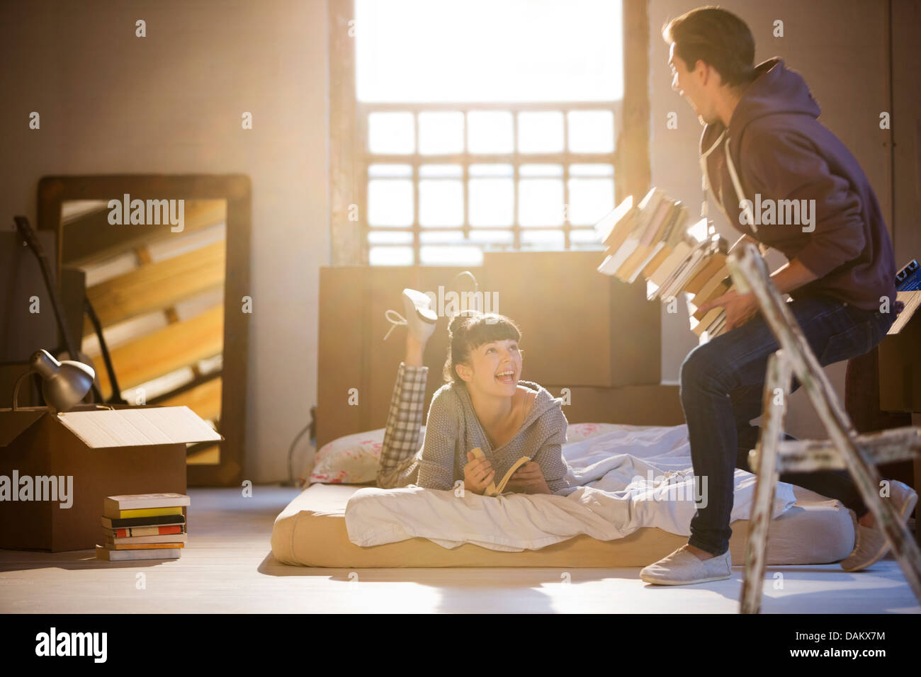 Couple relaxing in attic - Stock Image