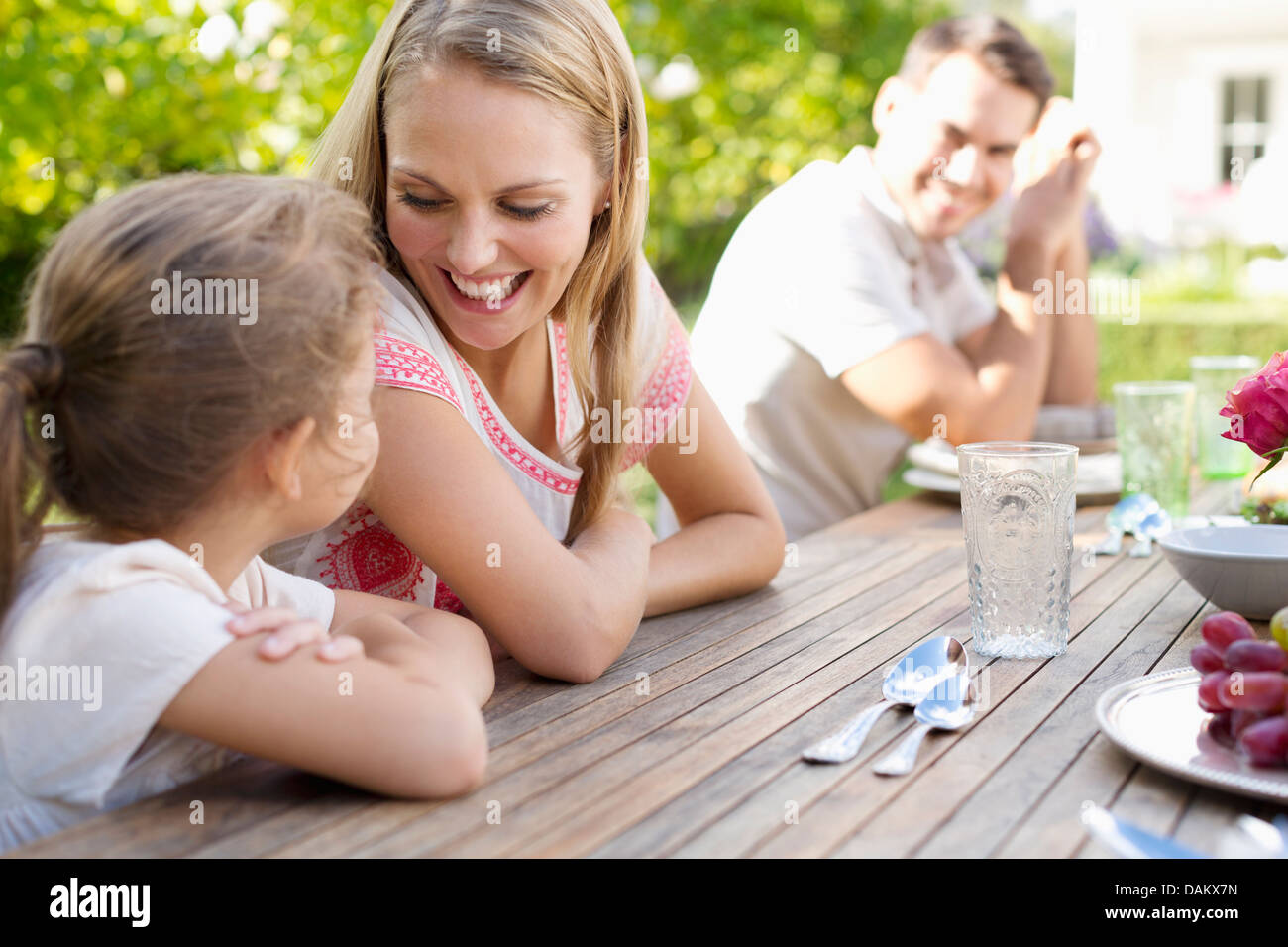 Family sitting at table outdoors - Stock Image