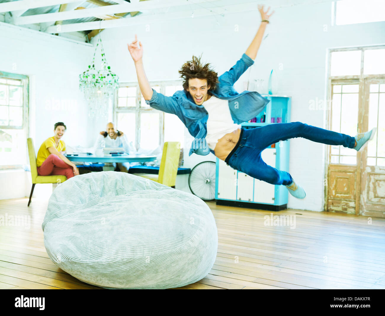 Man jumping into beanbag chair - Stock Image