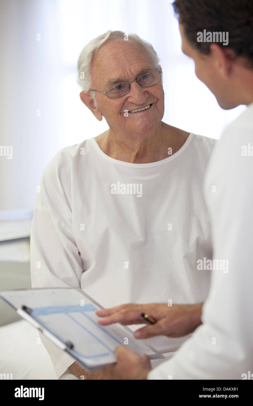 Doctor talking with older patient in hospital room - Stock Image