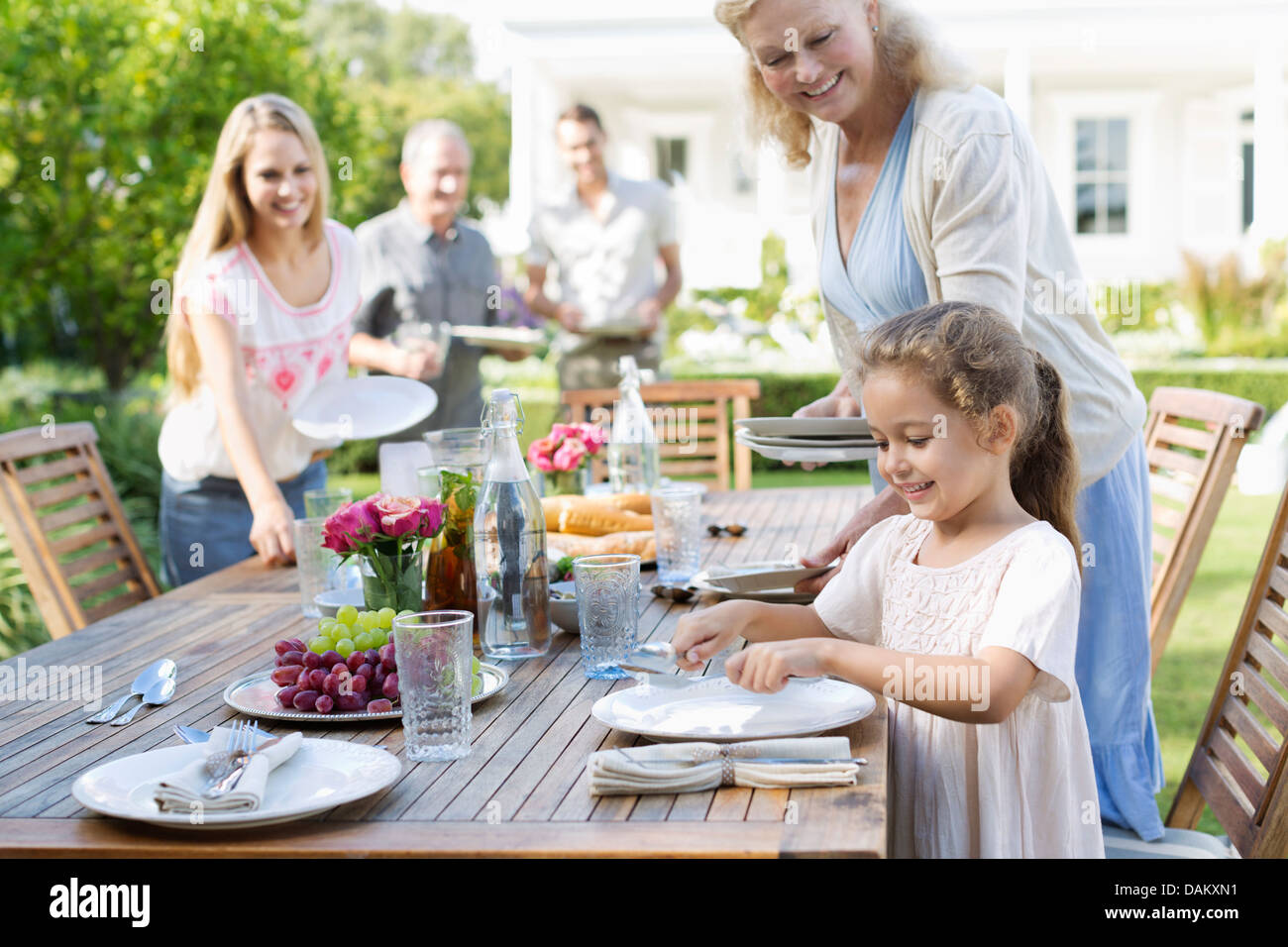 Family setting table outdoors - Stock Image