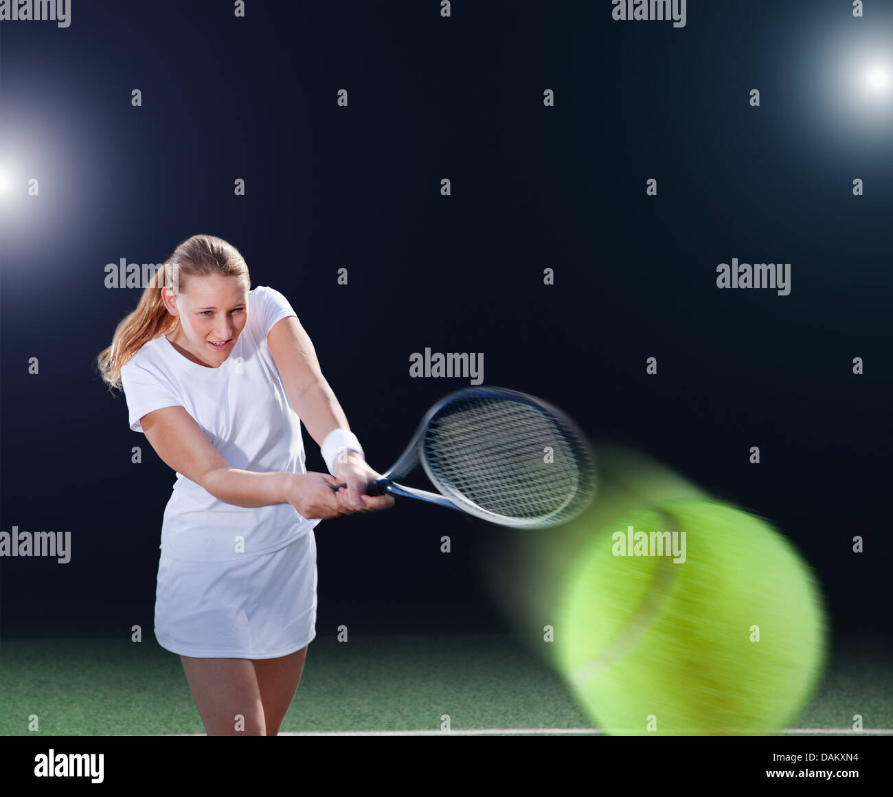 Tennis player hitting ball on court - Stock Image